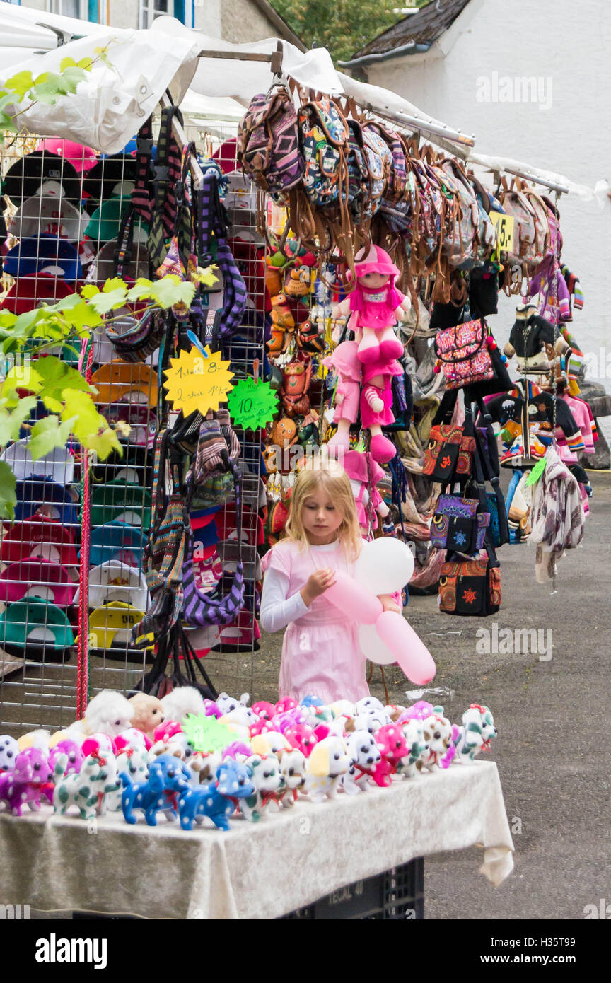 A small girl running with balloons at a handicrafts stall, Street wine festival,  Wolf, near Traben Trarbach, Mosel, - Stock Image