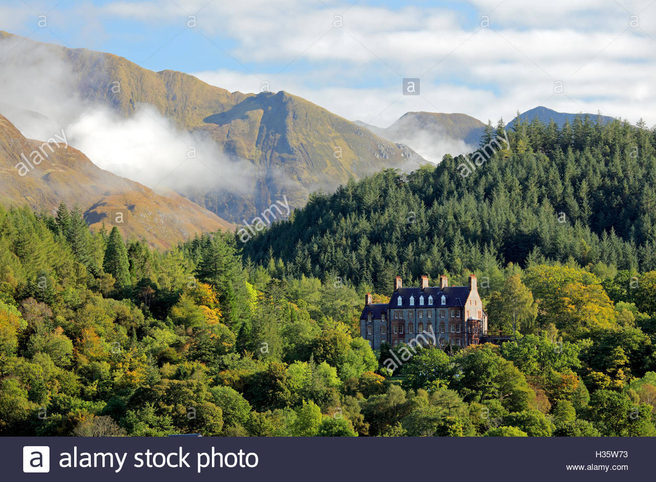 A picturesque view from the shore of Loch Leven looking over to Glencoe house. Ballachulish, Scotland. - Stock Image
