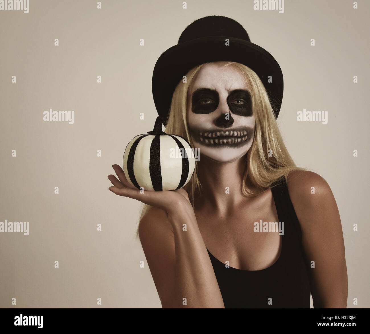 A blond girl is wearing scary skeleton makeup paint on her face. She is holding pumpkin decor for a halloween message - Stock Image