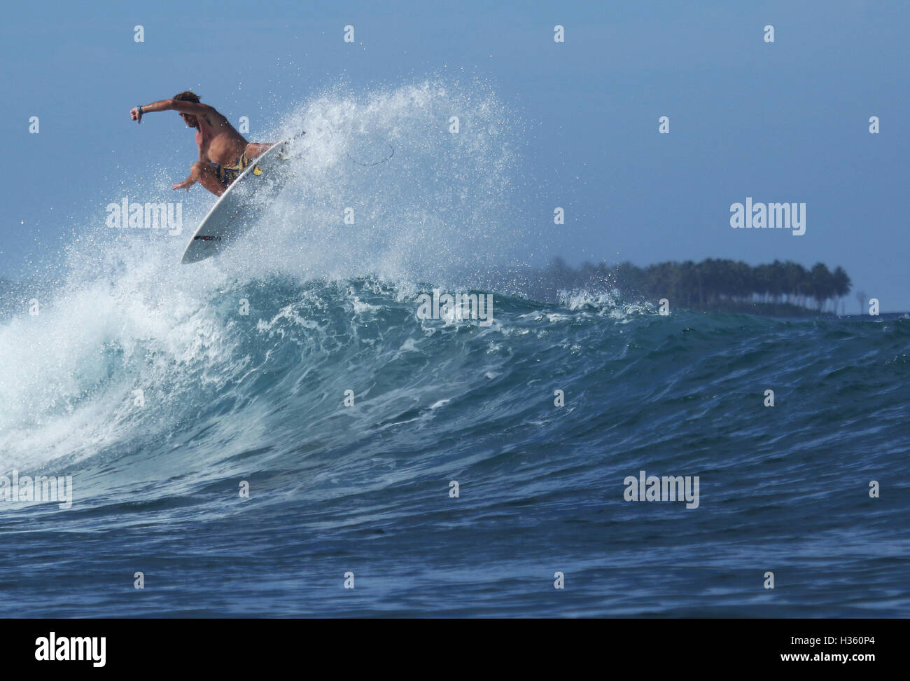 Surfer flying over a wave at Macaronis, Mentawai Islands - Stock Image