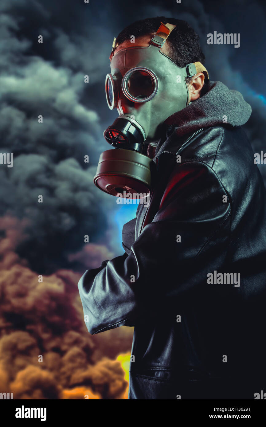 Armed man with gas mask over explosion background Stock Photo