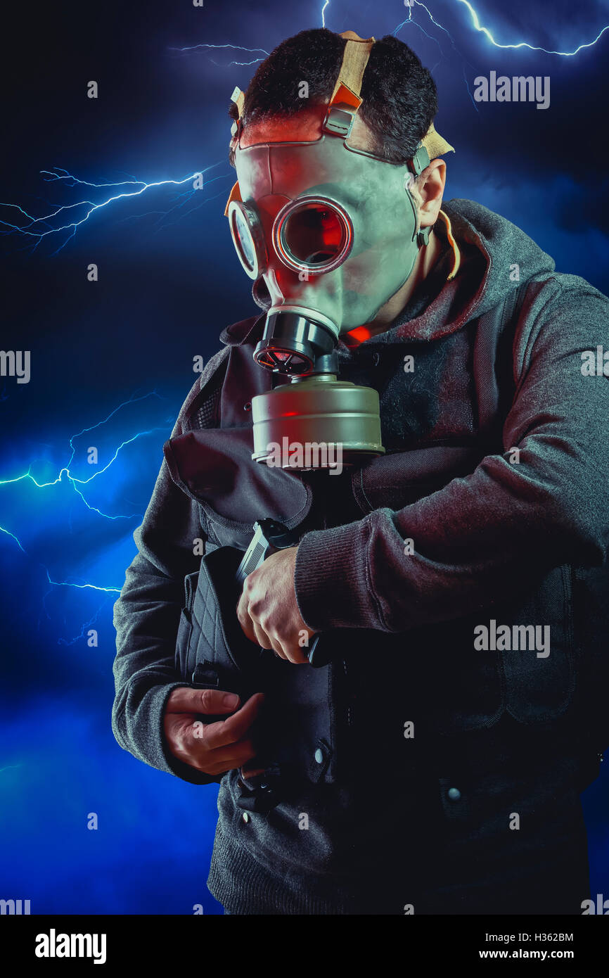 Man with long leather jacket and assault rifle over storm background Stock Photo