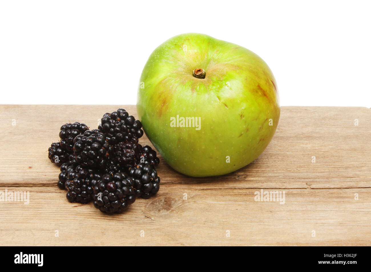 Blackberries and a Bramley cooking apple on rustic wood against a white background - Stock Image