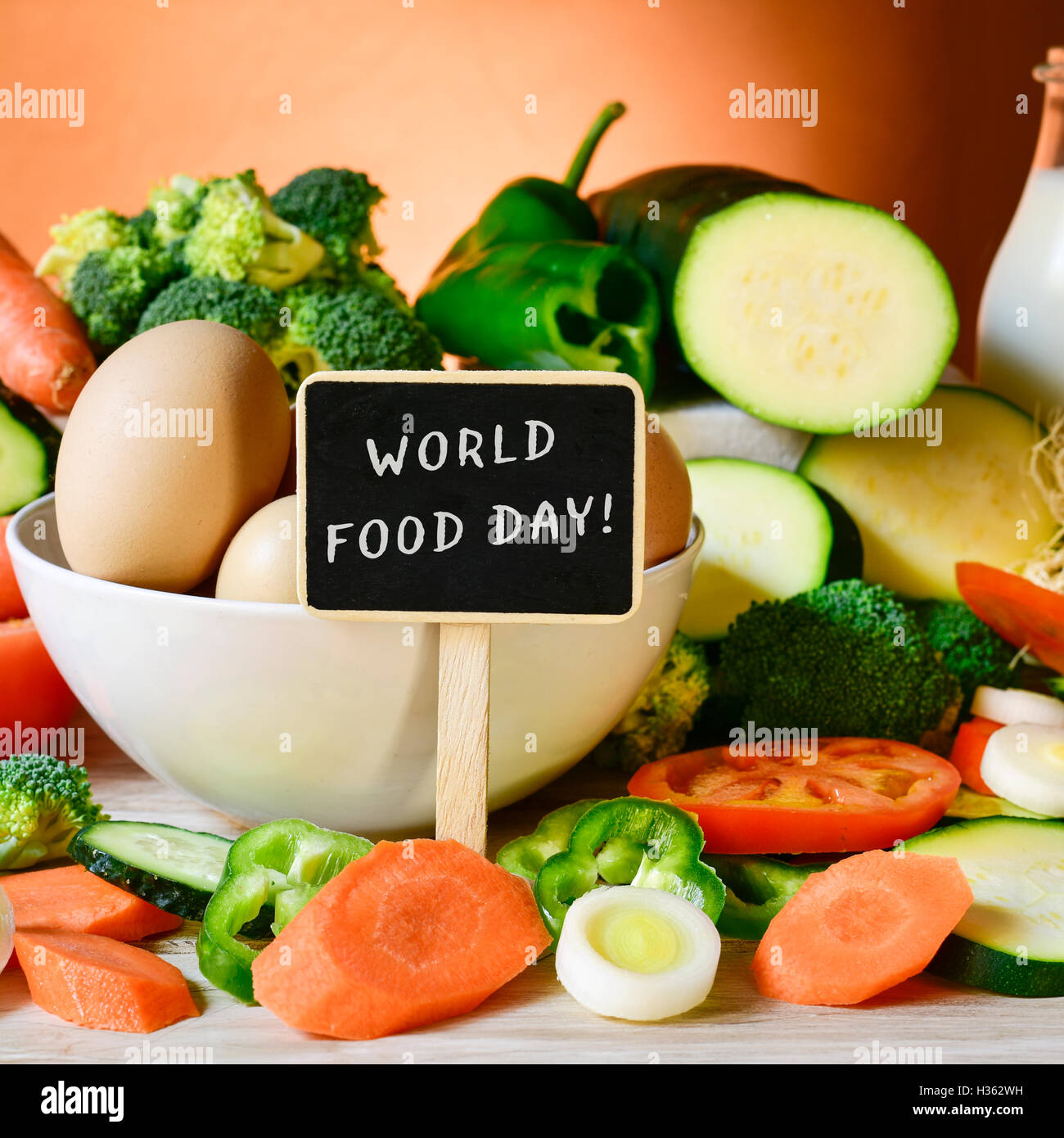 closeup of a chalkboard with the text world food day placed on a table fool of food, such as eggs, milk and pile - Stock Image