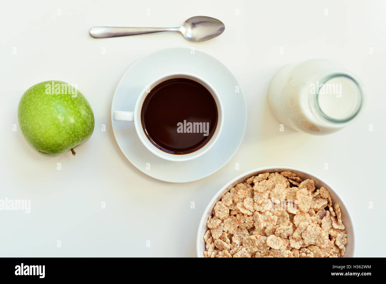 high-angle shot of a white table set for breakfast with a green apple, a cup of coffee and a bowl with cereals - Stock Image