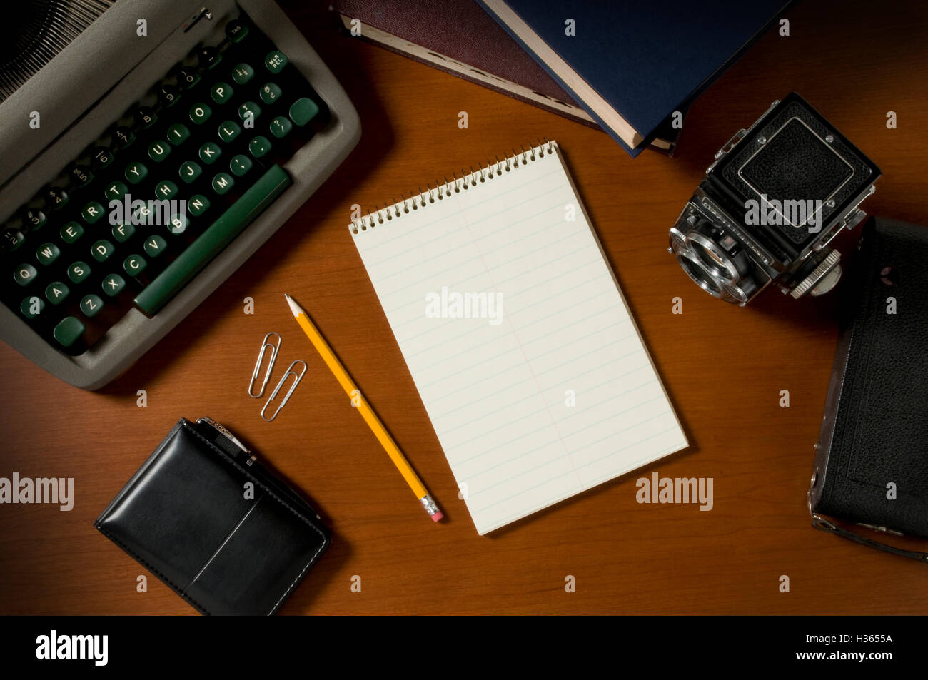 Blank steno notepad on a wooden desktop among vintage journalism props, including a typewriter and film camera - Stock Image