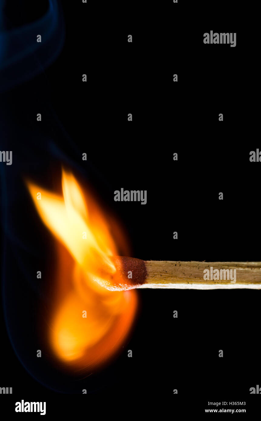 Match beginning to burst into flame isolated on black background - Stock Image