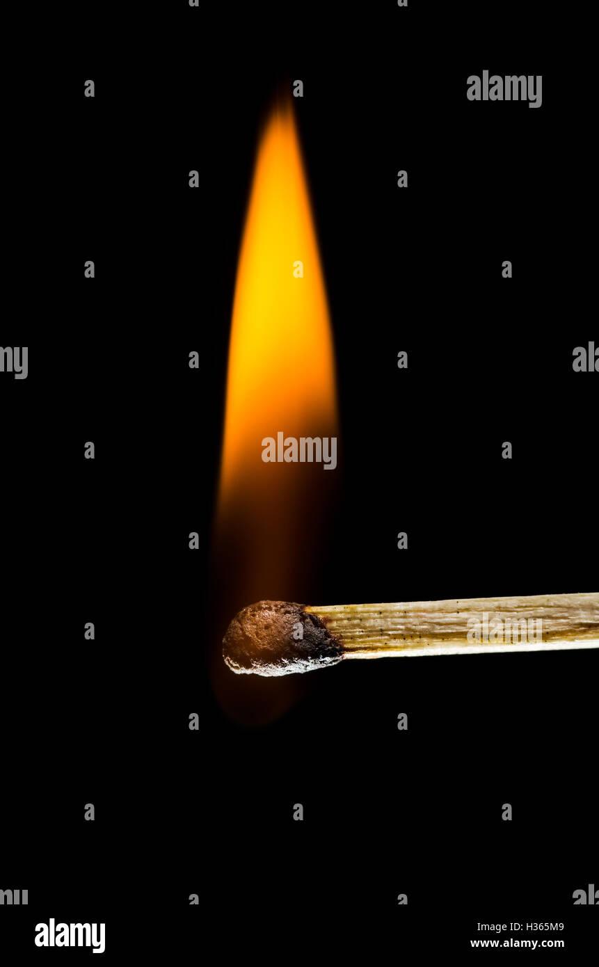 Matchstick burning isolated on black background - Stock Image