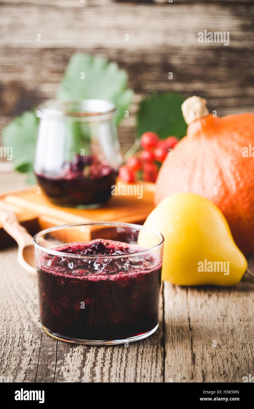 Homemade thanksgiving cranberry sauce in glass on woonen table - Stock Image