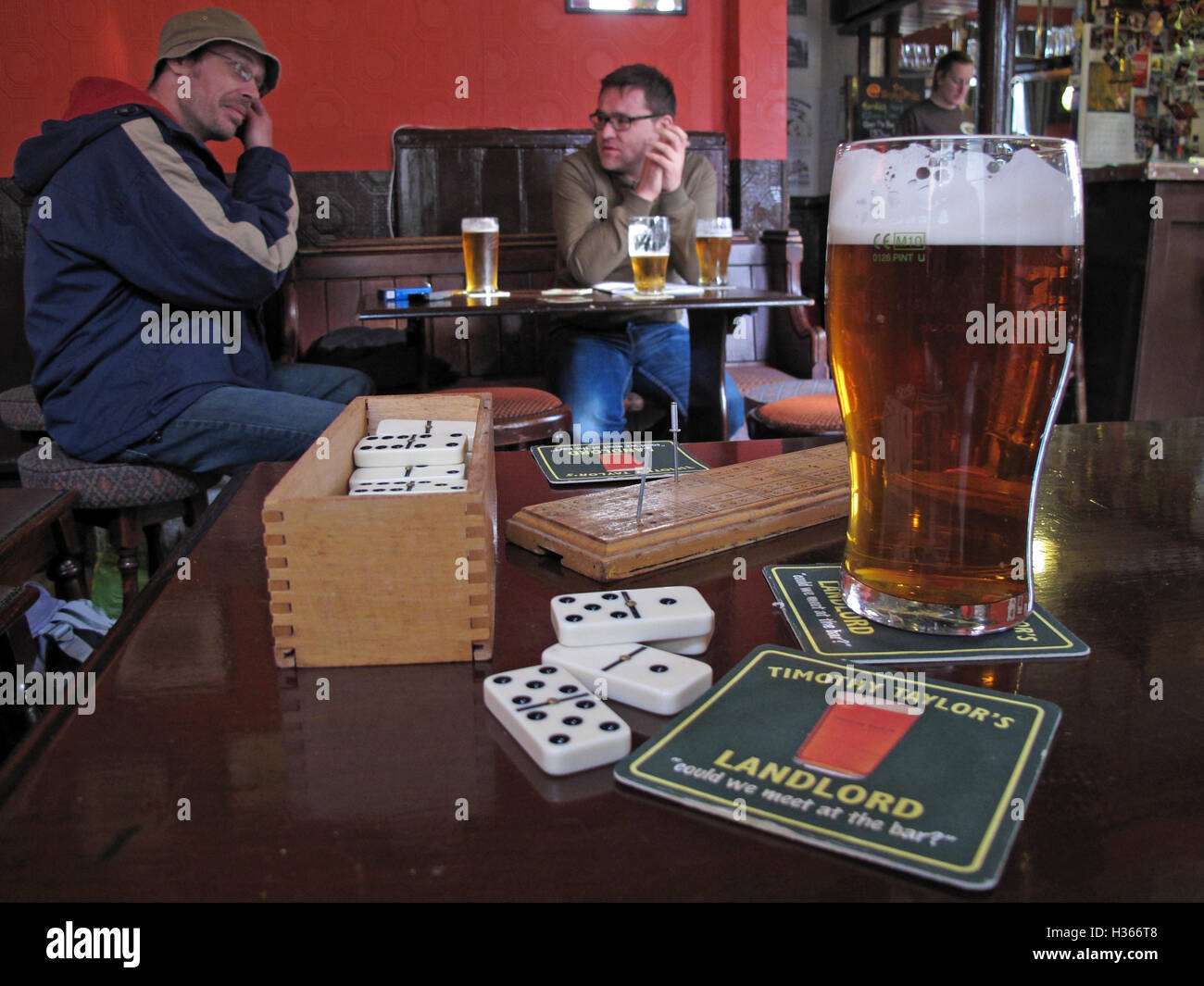 Traditional Pub English Games, dominos with drinkers and pint of Timothy Taylor Landlord bitter, Shipley, Yorkshire, - Stock Image