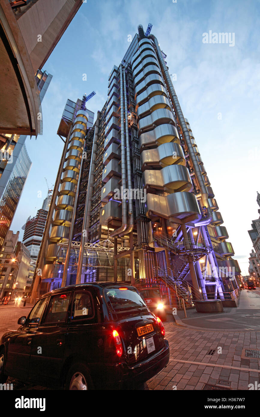 Lloyd's building London at dusk, Lime St, England, with black taxi cab - Stock Image