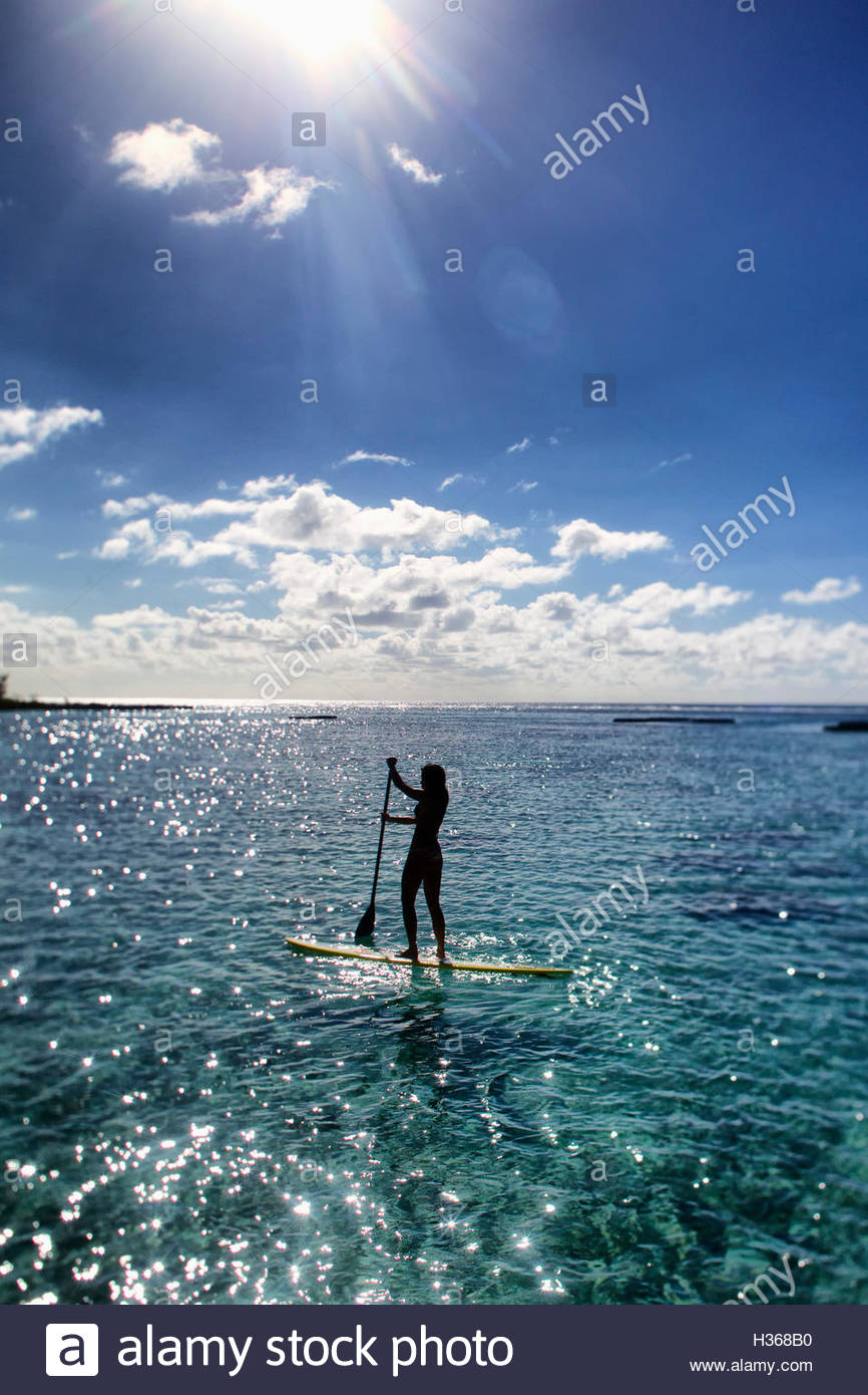 young woman stand up paddling in shimmering light - Stock Image
