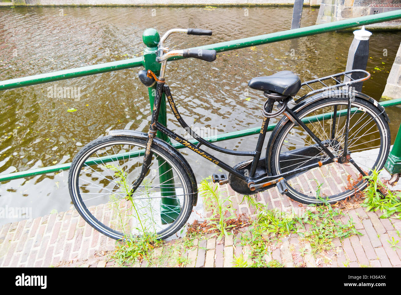 Old bicycle parked by railing on quayside of canal - weed and cigarette butts on the street in downtown Leiden, Stock Photo