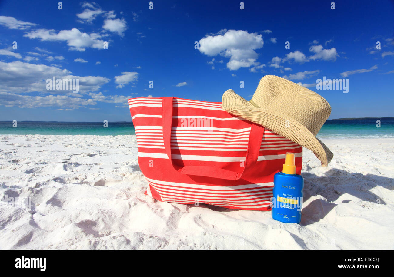Summertime sun protection sunscreen hat at the beach - Stock Image