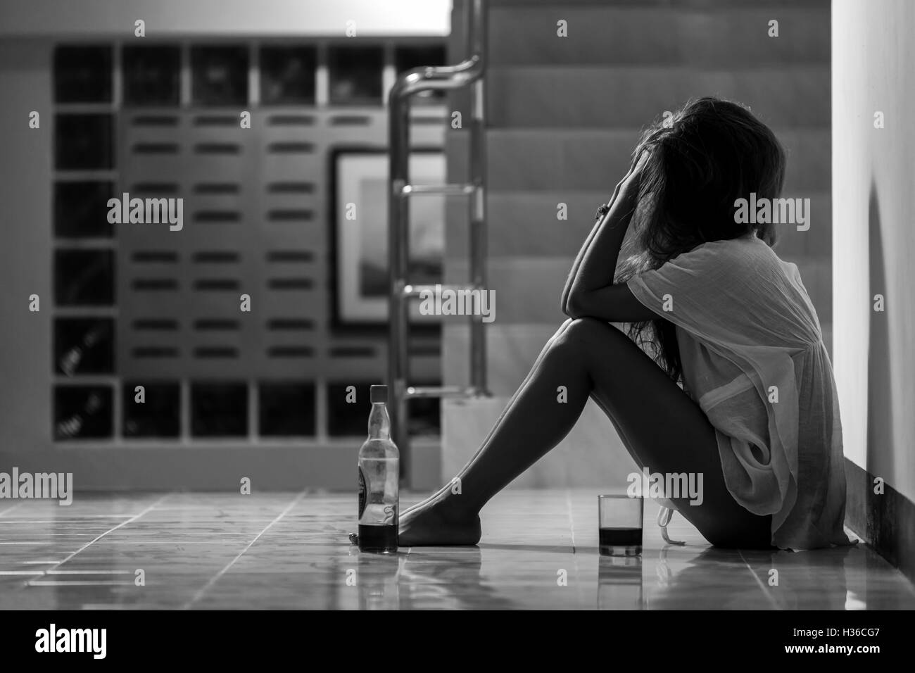 Girl in depression sitting on the floor with glass of wine - Stock Image
