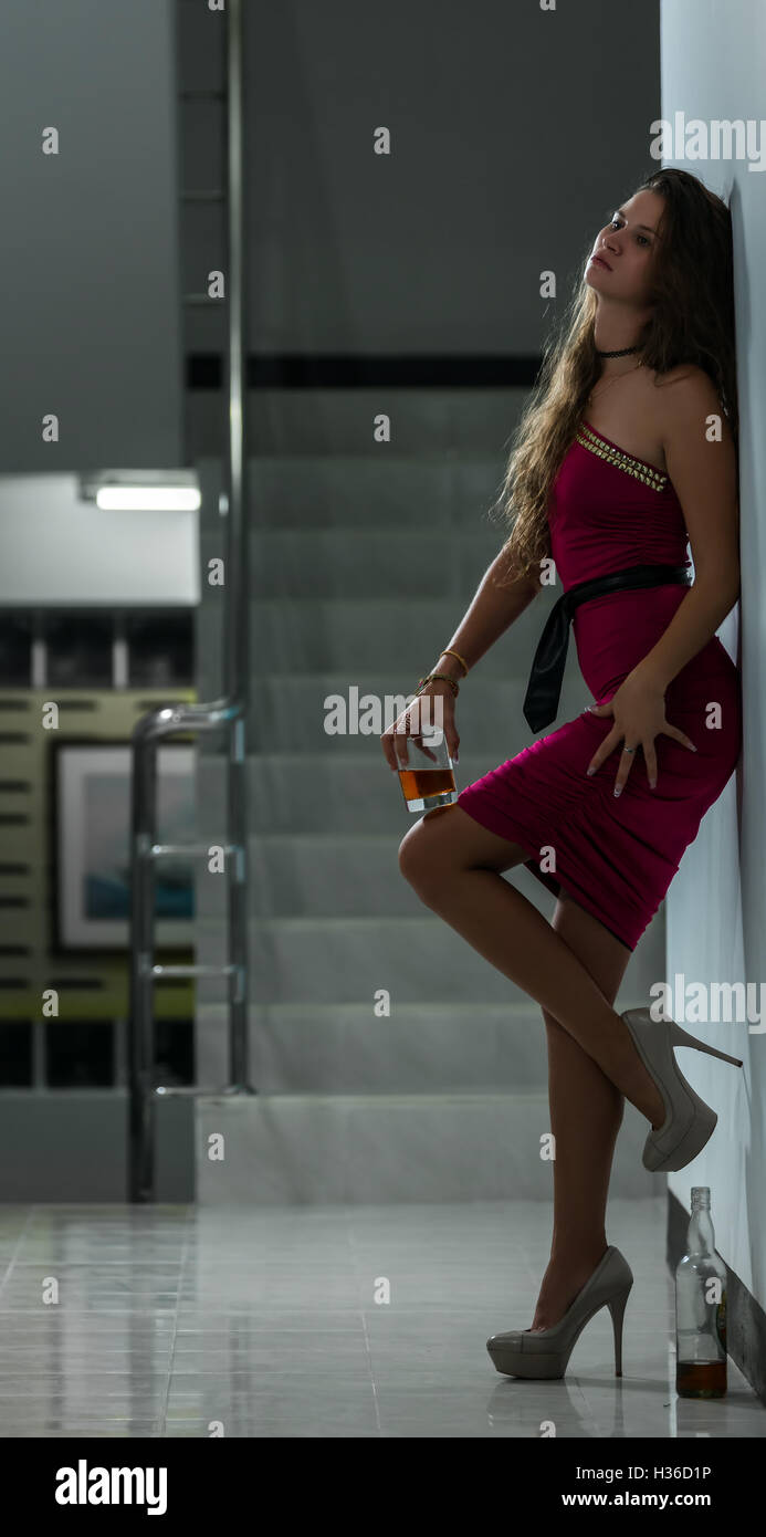 Girl in depression standing in a corridor and drinking alcohol in solitude - Stock Image