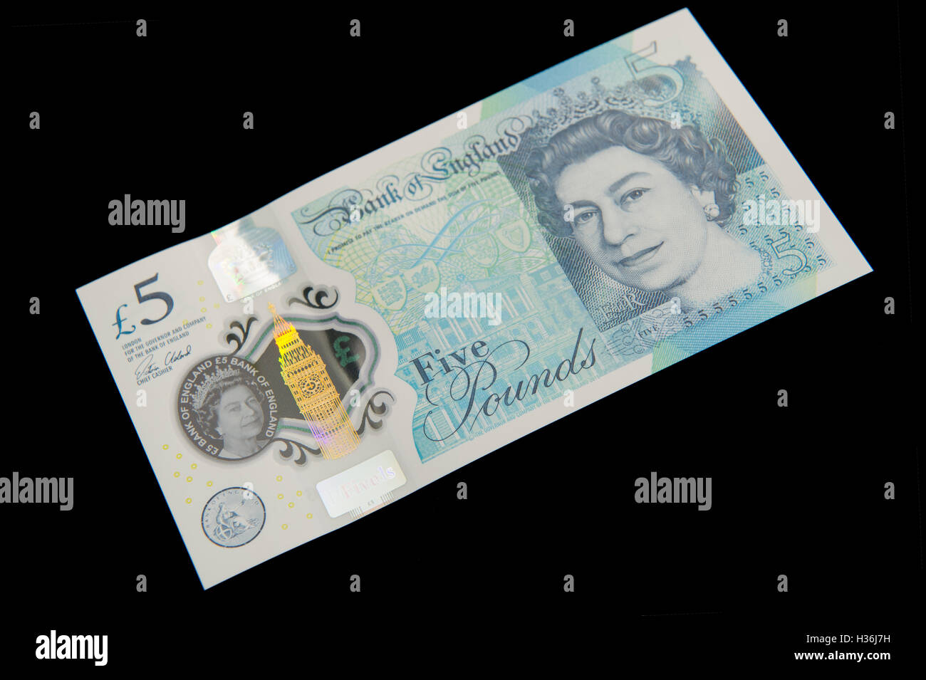 Front view of the new plastic (polymer) five pound note on a black background - Stock Image