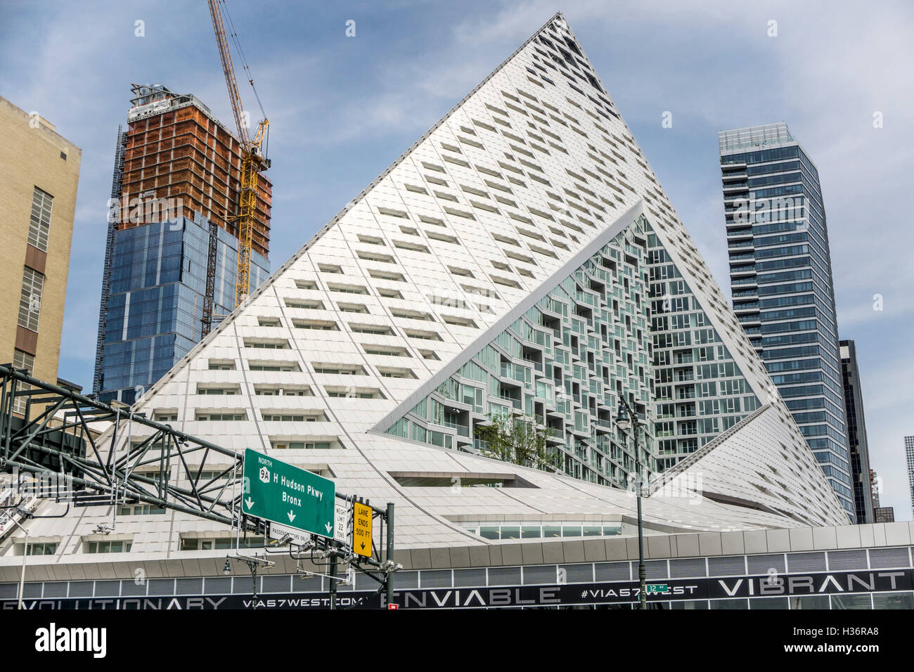 striking pyramidal form of luxury rental apartment high rise Via 57 West dominates  Hudson river waterfront skyline - Stock Image