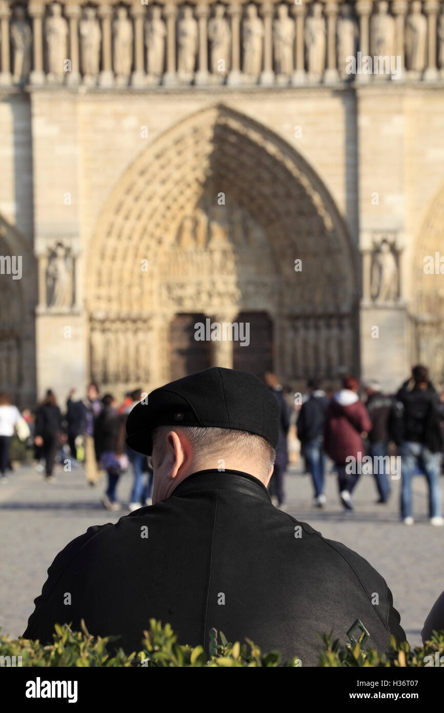 Man taking a break at the Place du parvis notre dame square with Notre Dame Cathedral in the background.Paris.France Stock Photo