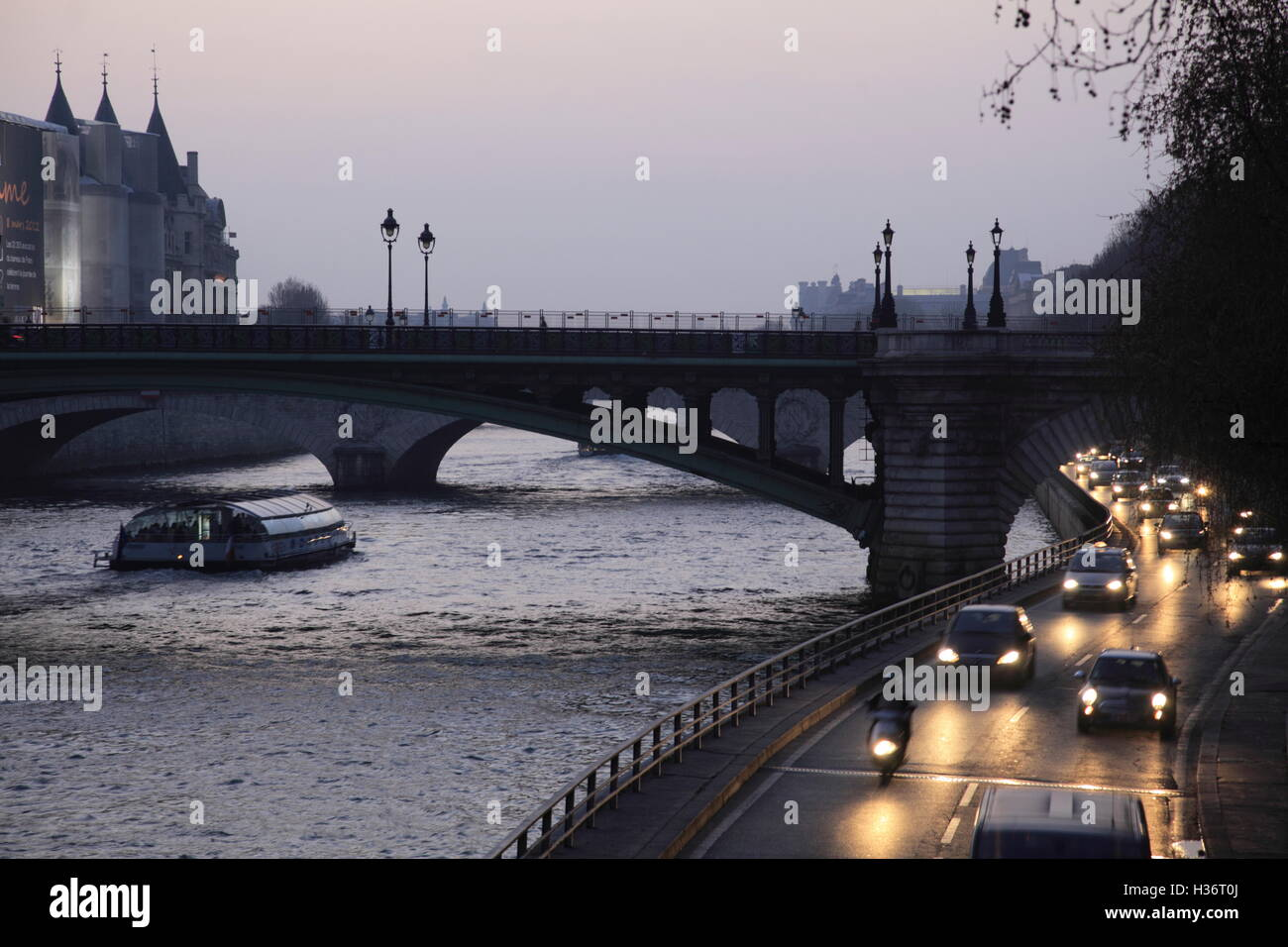 The twilight view of riverside traffics and Pont au Change over River Seine in background. Paris.France - Stock Image