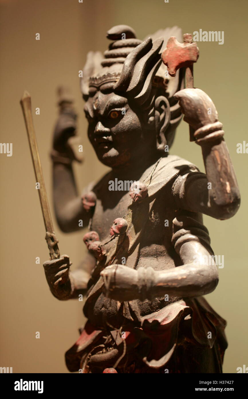 An antique statue of a Japanese deity display in Galeries du Pantheon Bouddhique of Museum Guimet Paris.France - Stock Image