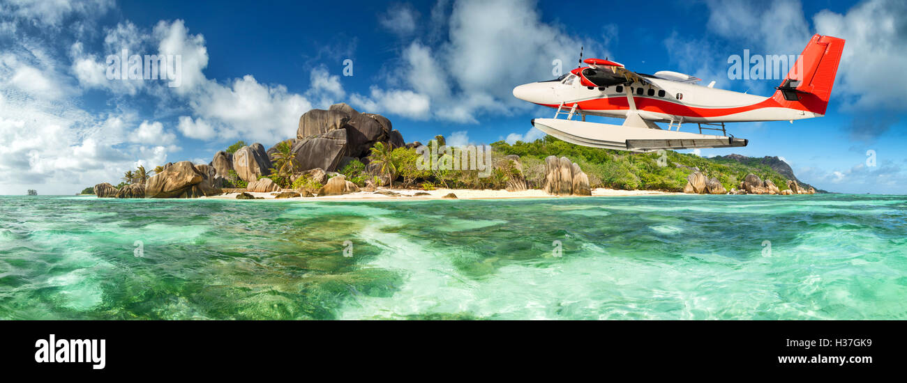 Beautiful Seychelles tropical beach Anse Source D Argent at La Digue island with flying seaplane - Stock Image