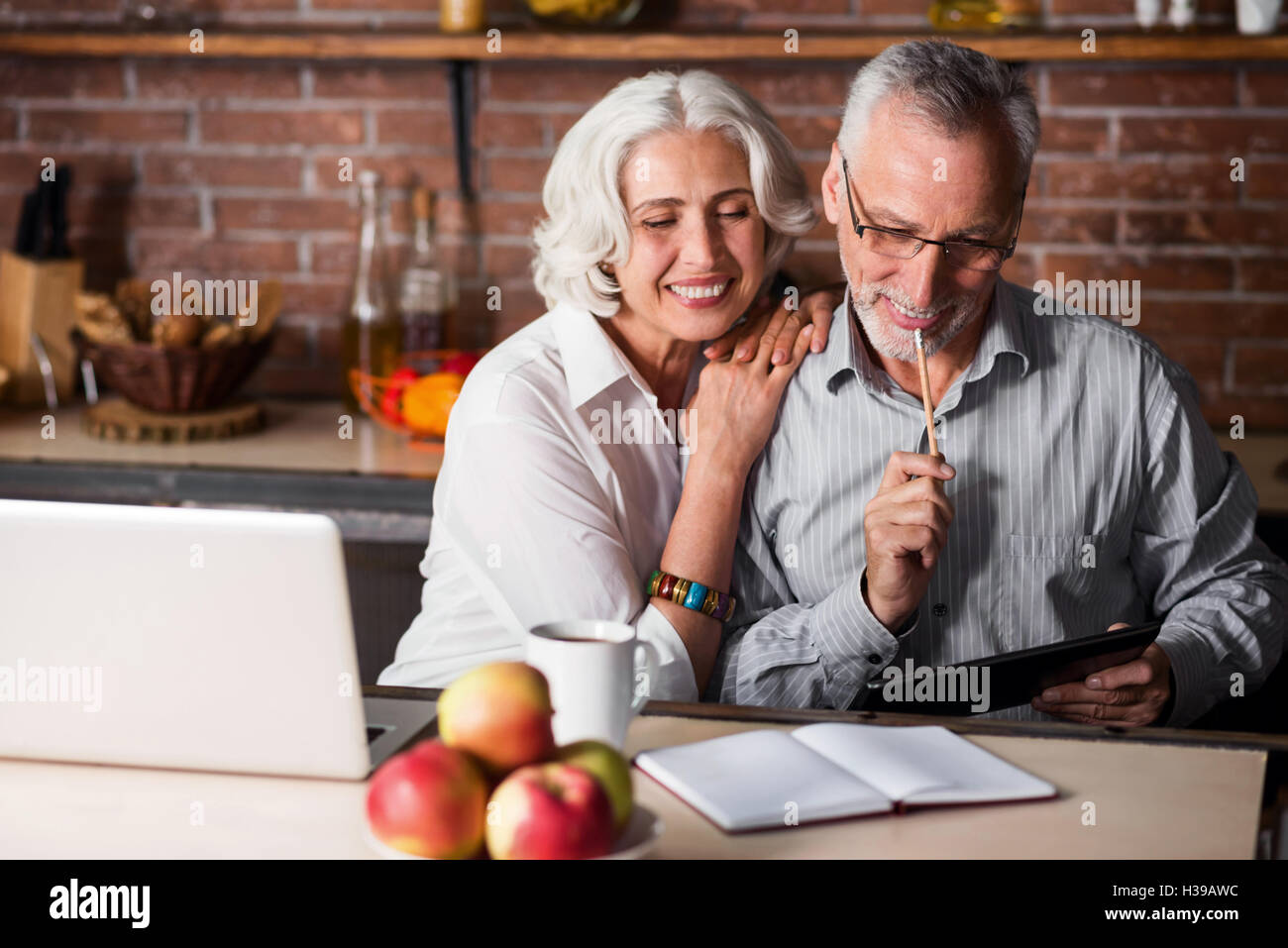 Elderly couple making notes in a kitchen - Stock Image