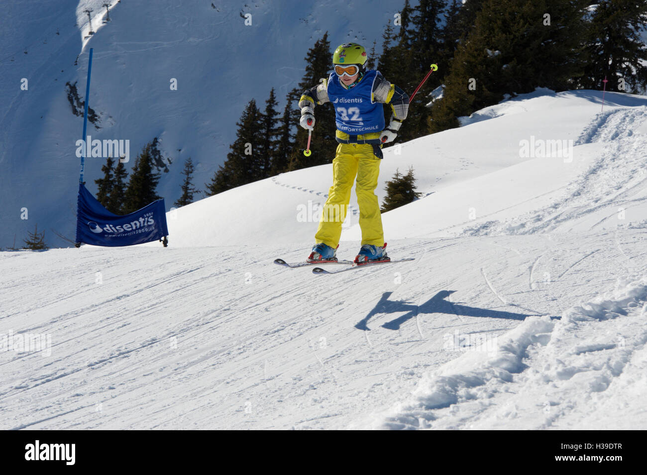 A boy skiing over a piste during a kids race - Stock Image