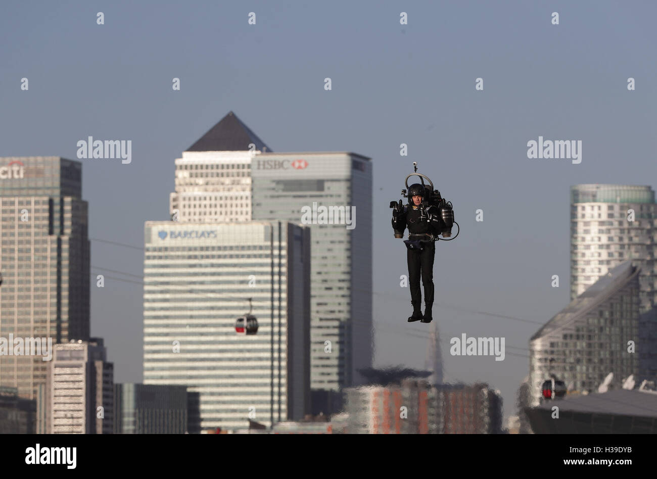 Against the backdrop of the Canary Wharf, pilot David Hayman makes a flight in a jetpack over the Royal Docks in - Stock Image