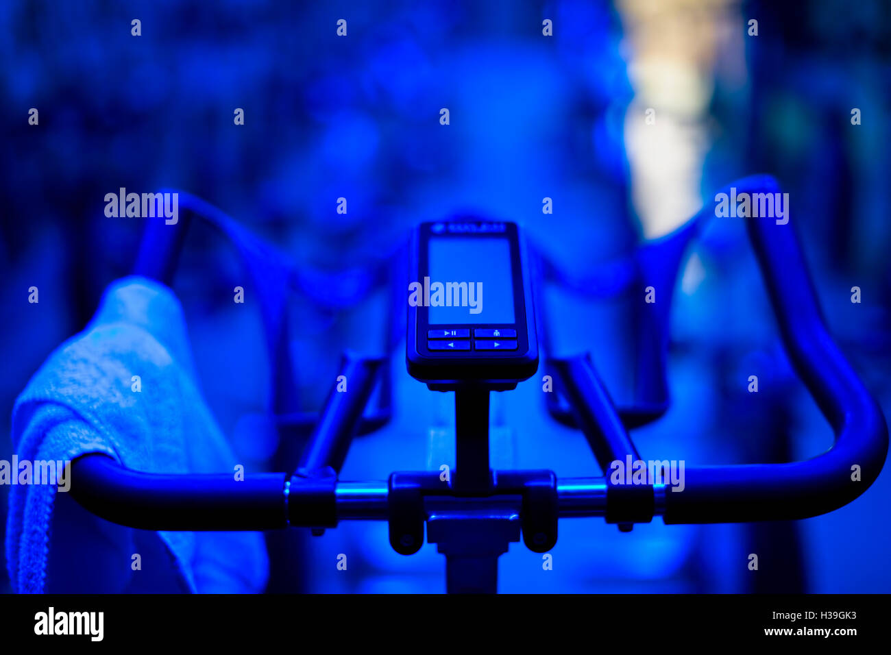RPM Bike in a Group Exercise Studio with blue light and a towel on the handlebar - Stock Image