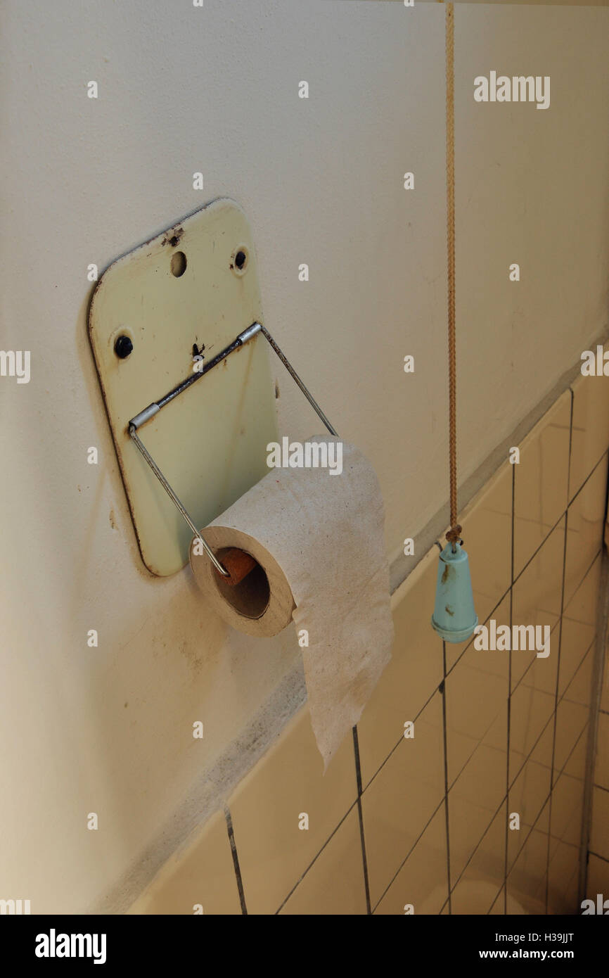 Vintage lavatory interior. Toilet paper and toilet paper holder. - Stock Image