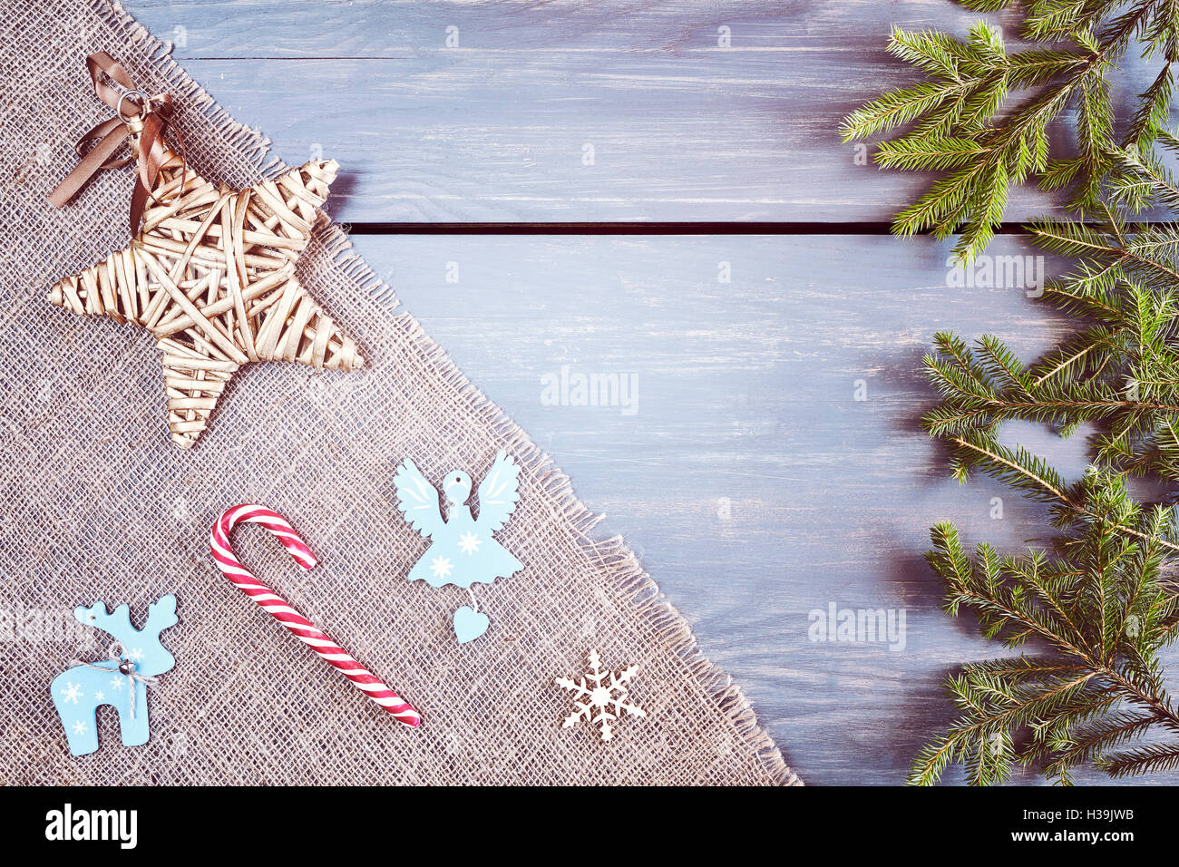 Retro stylized Christmas background, spruce branches with decorations on a rustic wooden table, top view with copy - Stock Image