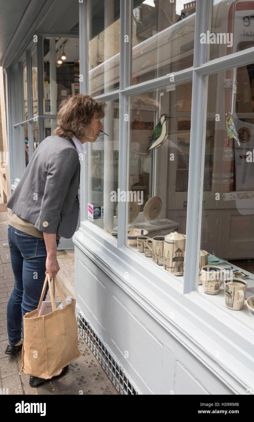 Lady looking into shop window, Cambridge, UK Stock Photo
