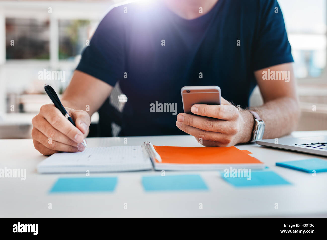Close up shot of a man taking down note in a personal organizer with mobile phone in other hand. Young man hands - Stock Image