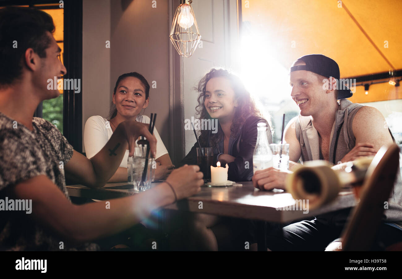 Group of friends sitting in cafe and having fun. Teenagers relaxing on coffee shop. - Stock Image