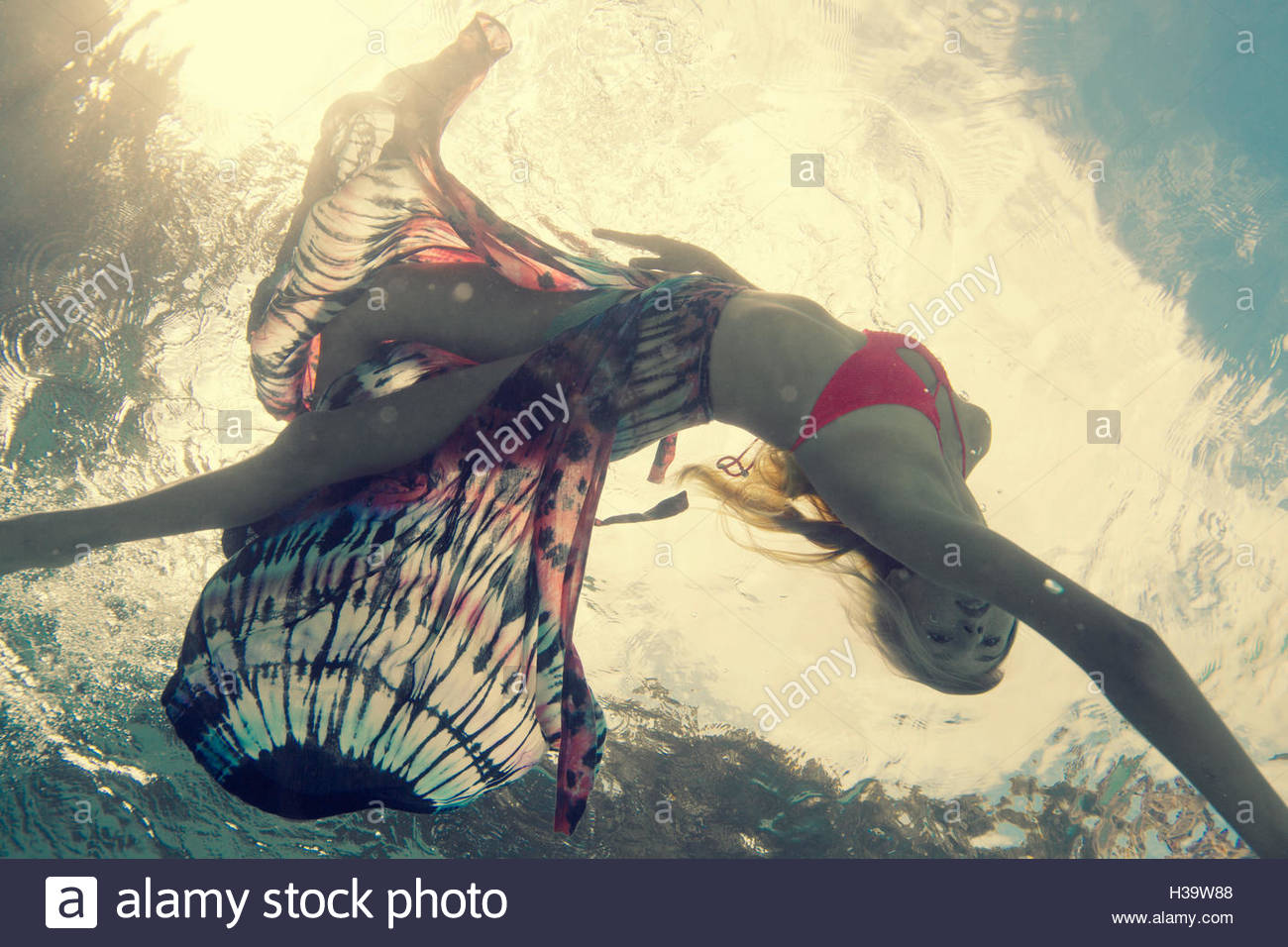 underwater shot of a young woman swimming in a pool - Stock Image