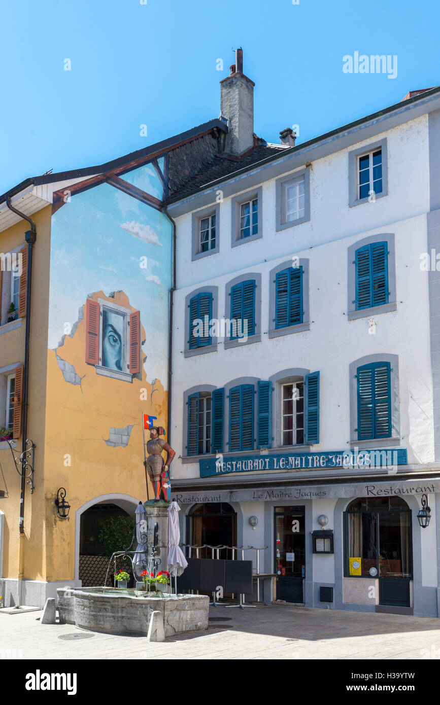 Statue of Maître Jacques and mural painting, fountain with potable water, Nyon, canton Vaud, Switzerland - Stock Image