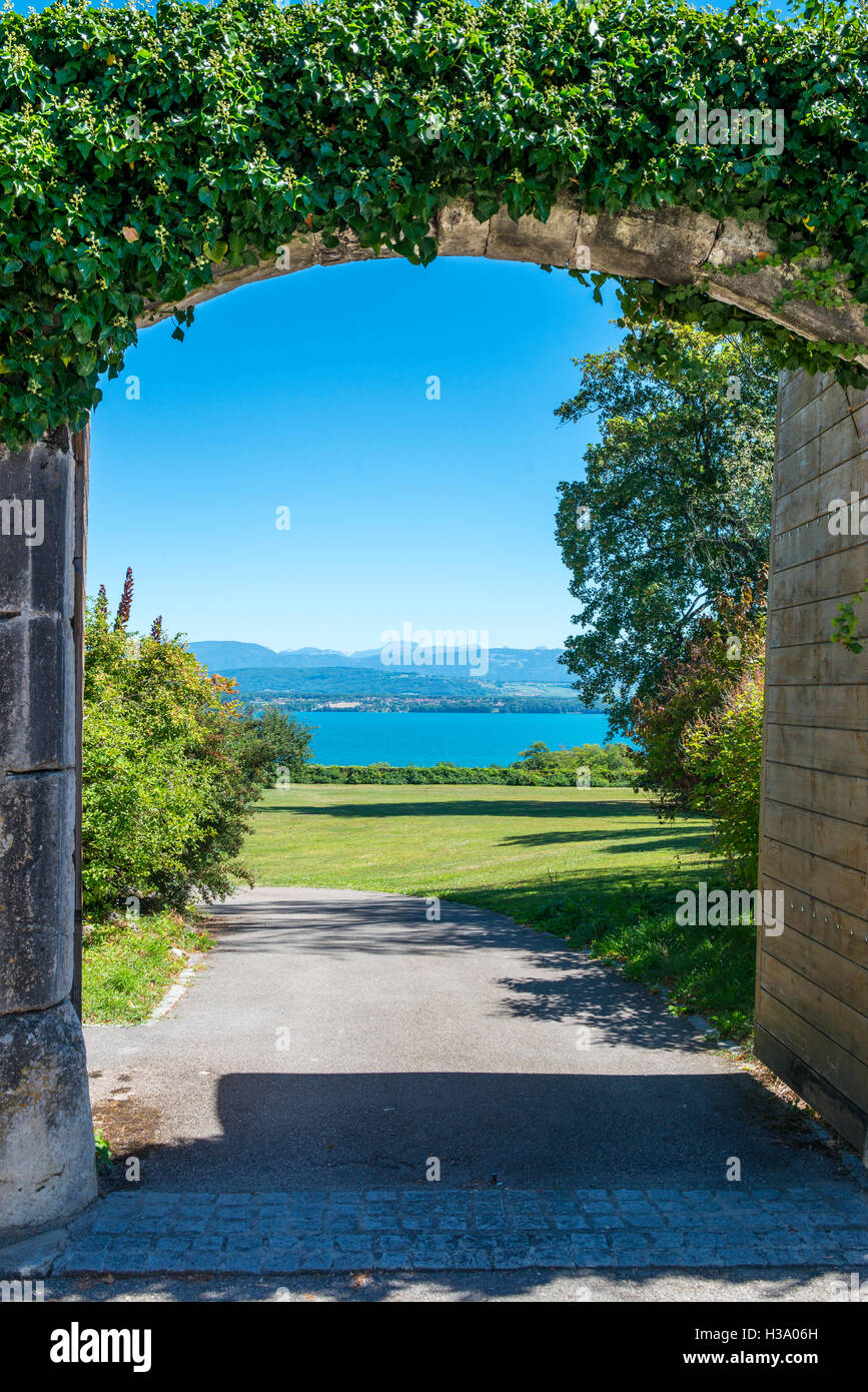 View of Lake Geneva through an open gate in a stone wall covered with ivy, Nyon, canton Vaud, Switzerland - Stock Image