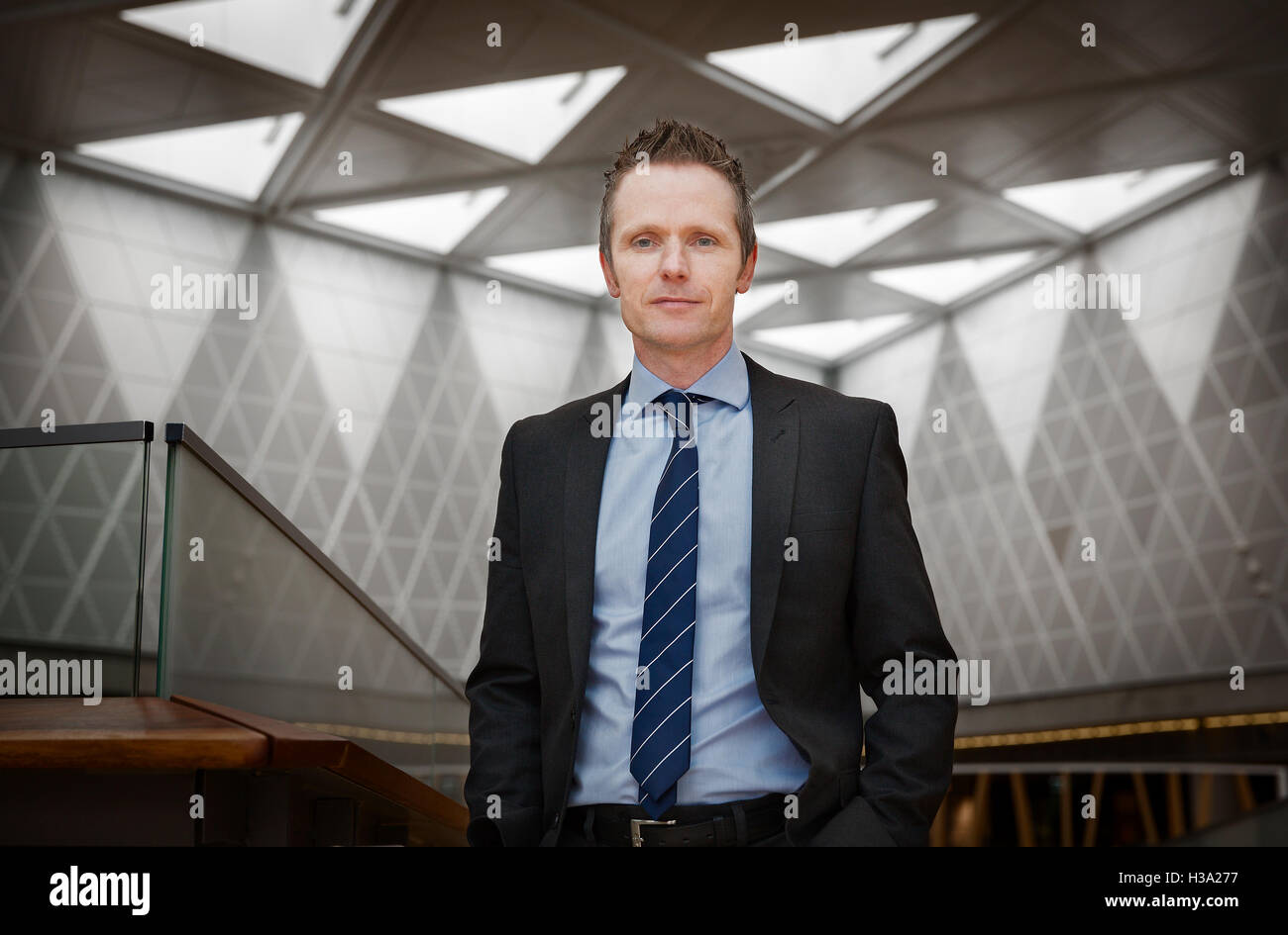 Confident businessman standing in a corporate building. - Stock Image