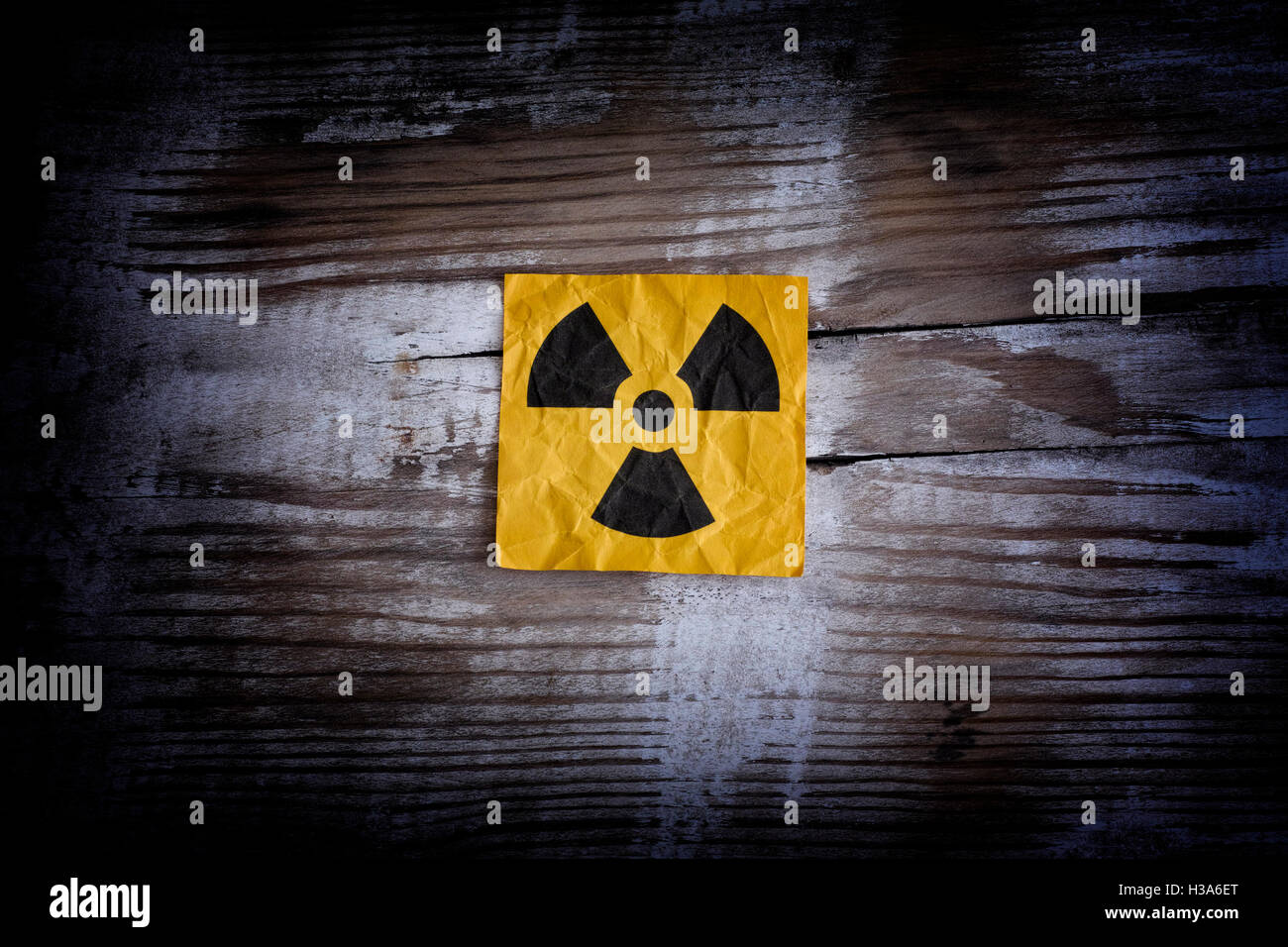 Radiation warning sign on a wooden surface. Close up. - Stock Image