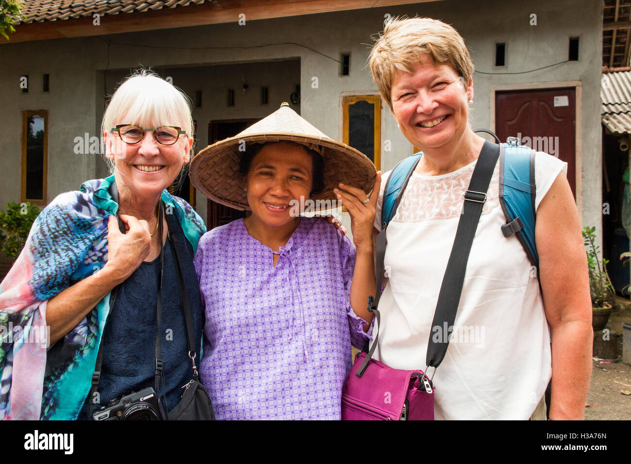 Indonesia, Lombok, Mantang, rural village, woman wearing conical hat with western tourists - Stock Image