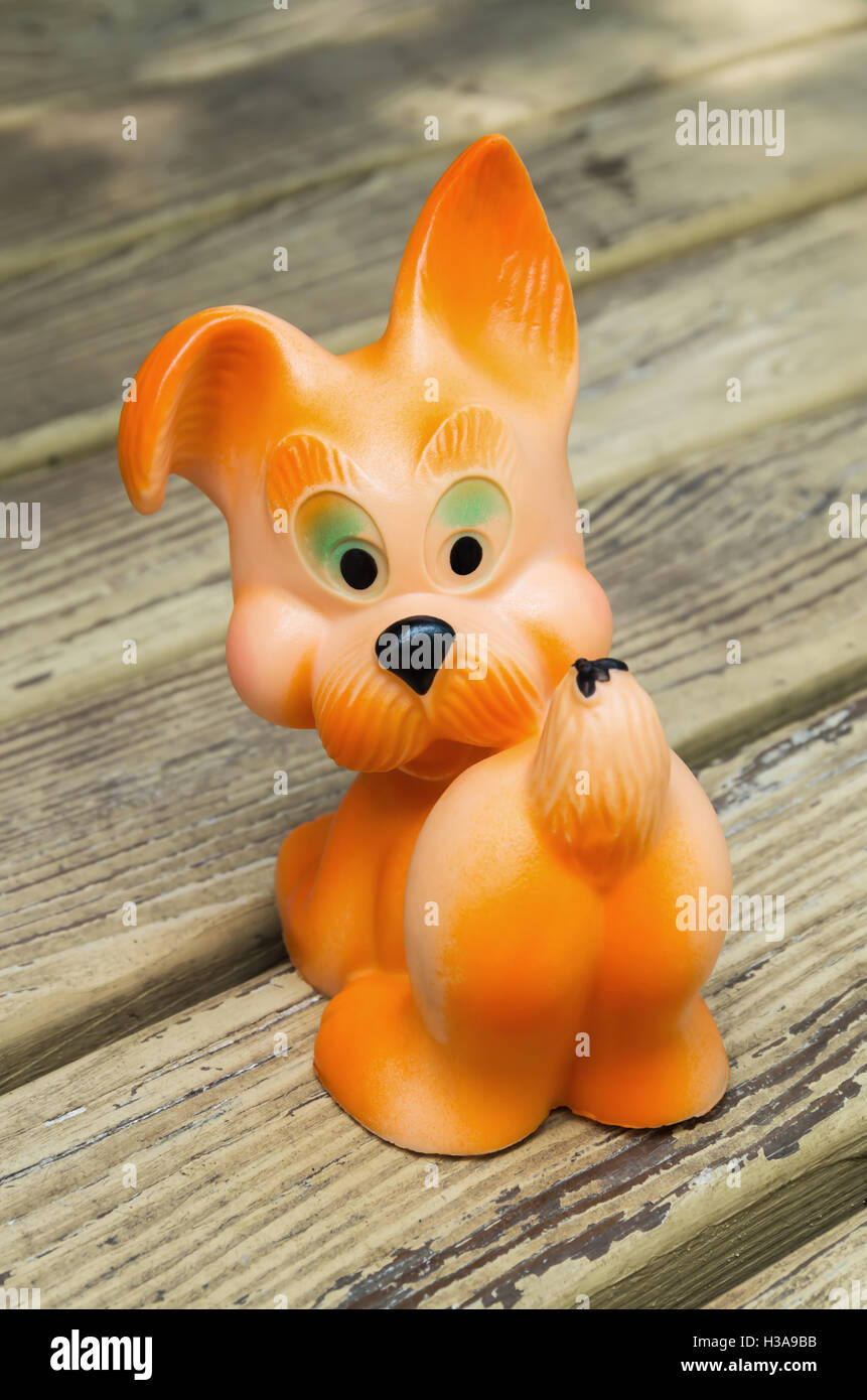 Rubber dog toy for young children orange color - Stock Image