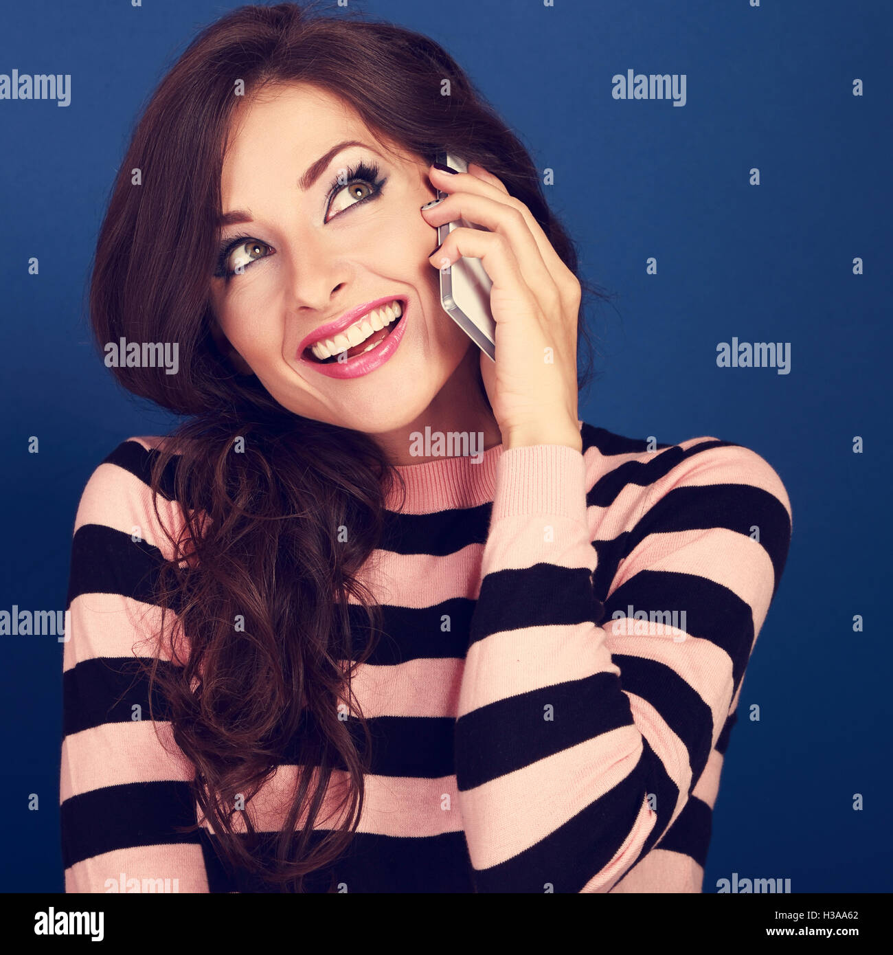 Beautiful makeup excited woman talking on mobile phone and with thoughtful look looking up on bright blue background. Stock Photo