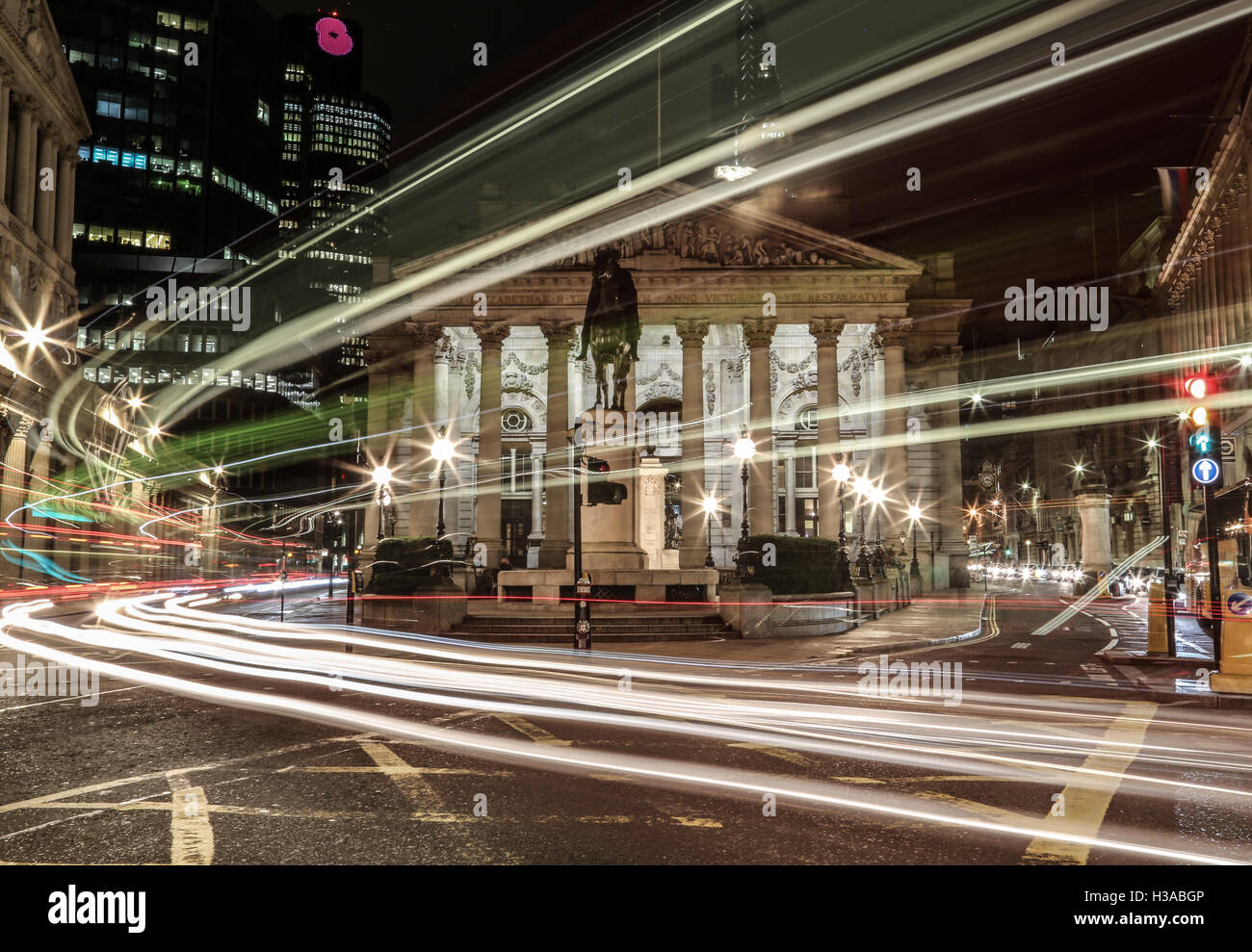 Long exposure shot of Bank Station at night, crossed by streaked lights from a passing double decker bus in London. - Stock Image