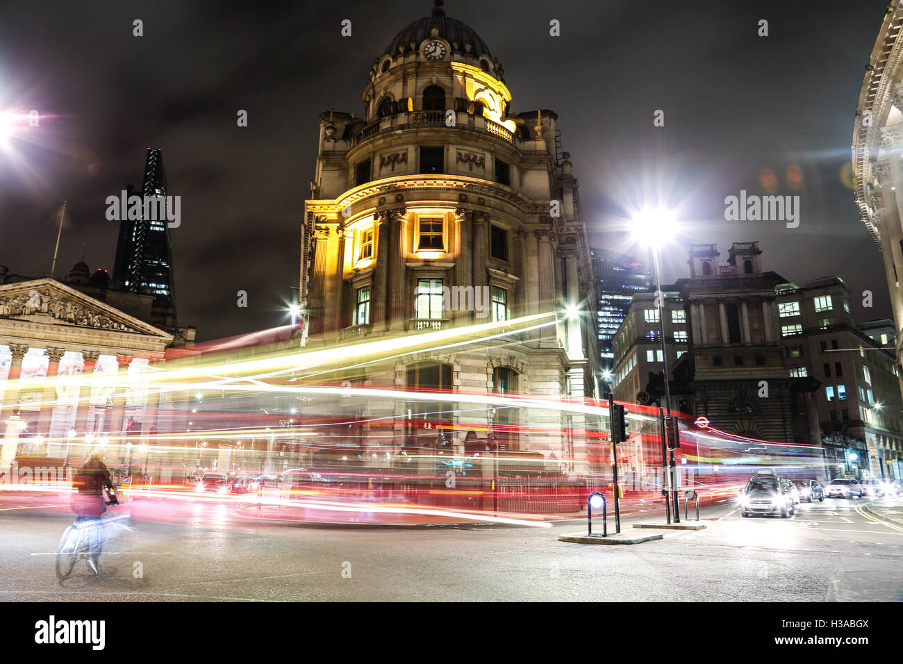 Bank and Monument Station at night, with a cyclist making his way through the streaks of traffic lights. - Stock Image