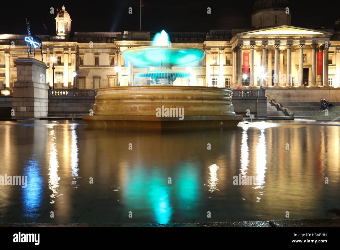 Trafalgar Square and the National Gallery in London at night, with lights and reflections on the fountain surface. - Stock Image