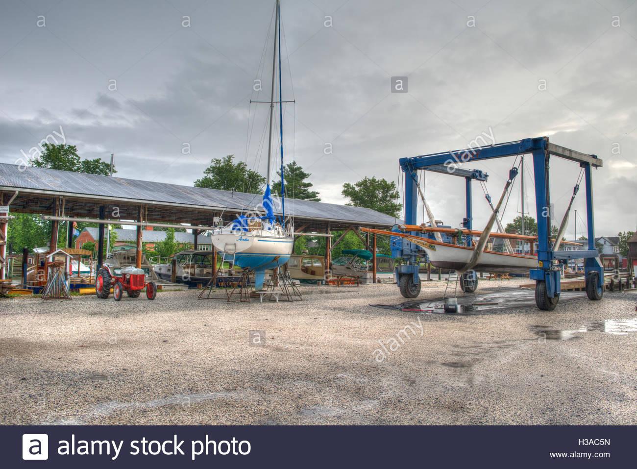 A sailboat, log canoe, and boat lift in a shipyard. - Stock Image