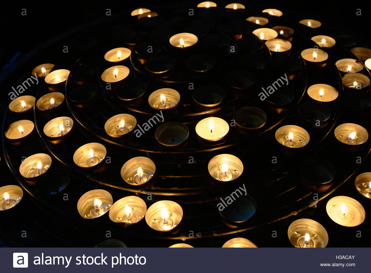 Votive candles in concentric circles inside the historic Notre Dame cathedral in Paris. - Stock Image