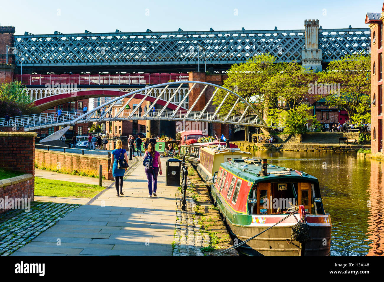 Strollers by the Bridgewater Canal Castlefield Manchester with the modern Merchant's Bridge and Victorian railway - Stock Image