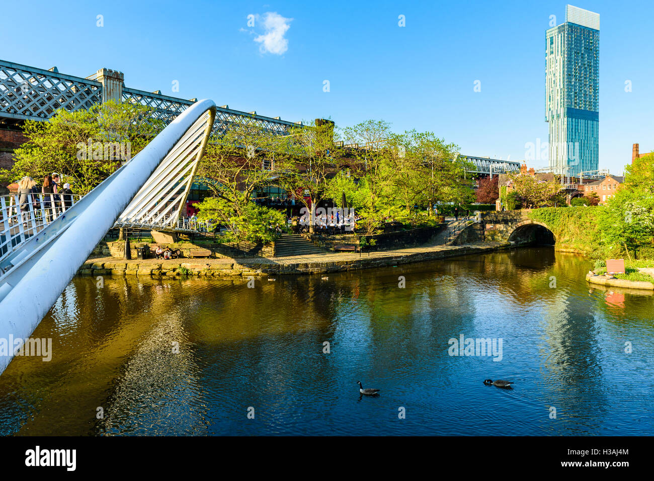 The Merchant's Bridge Castlefield Manchester with the Beetham Tower on the skyline - Stock Image